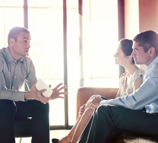Two people meeting with a financial advisor - Boyd Insurance