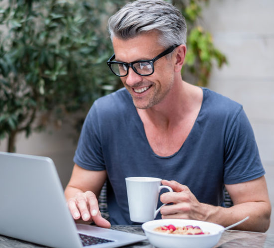 A man checking his laptop which eating breakfast - Boyd Insurance