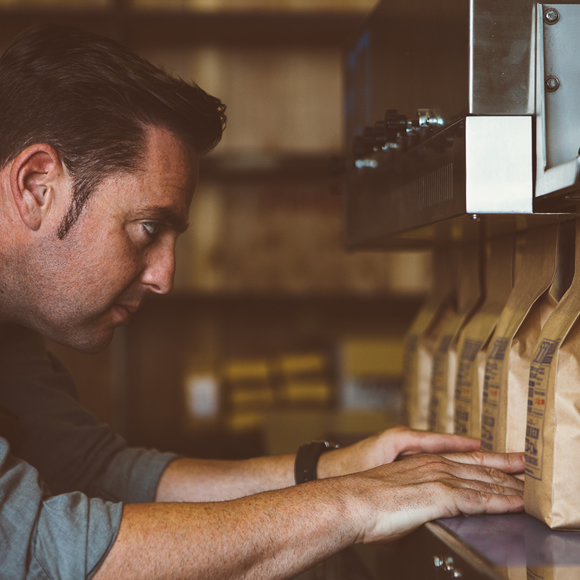 A man ensuring artisan coffee is correctly packaged - Boyd Insurance